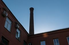 Ett fragment av en gammal tegelstenfabriksbyggnad med ett rör arkivbild