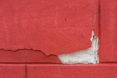 Ett fragment av en röd betongvägg med en original- spricka textur Bakgrund royaltyfri bild