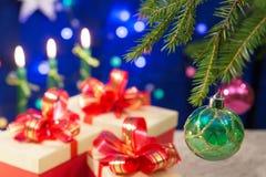 Ett fragment av ett träd för nytt år dekorerade med härliga bollar på tabellen är gåvor för ` s för nytt år Brännande stearinljus Royaltyfria Bilder