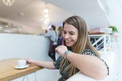 Ett frankt leende av ett härligt kvinnasammanträde i ett modernt kafé för en kopp av varmt kaffe Arkivfoto