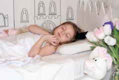 Ett fridsamt foto av en sova liten flicka med en krona på hennes huvud Arkivbild