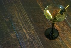 Ett fullt martini exponeringsglas med två oliv på en tandpetare står på en trätabell arkivbilder