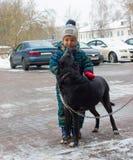 Ett fyraåringbarn, en pojke, står på en vintergata och att dalta en hund arkivfoto