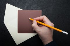 Ett fyrkantigt kuvert för post och en brun bokstav på en svart tabell En hand med en gul blyertspenna arkivbilder