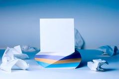 Ett fyrkantigt stycke av papper för anmärkningar som står på ett kvarter av papper I Arkivbilder