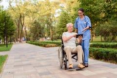 Ett gamal mansammanträde i en rullstol visar sjuksköterskan något på hans minnestavla Royaltyfria Bilder