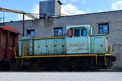 Ett gammalt drev med fraktbilar står på järnvägspåren i den saktade-ner zonen royaltyfri fotografi