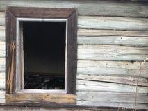 Ett gammalt förfallet fönster av ett träbyhus och en vägg av den förfallna journalen Arkivbild