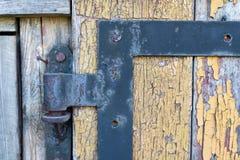 Ett gammalt gångjärn som monteras i dörren Gamla snickeristrukturer royaltyfria foton
