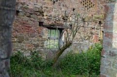 Ett gammalt herrelöst gods, en ruttnad grön fönsterram mot en vägg för röd tegelsten och en blå himmel arkivfoto