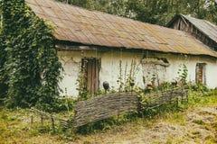 Ett gammalt hus med ett staket i en fattig by förstörd byggnad royaltyfri foto