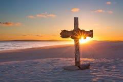 Ett gammalt kors på sanddyn bredvid havet med en lugna soluppgång Arkivfoto