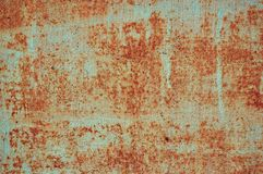 Ett gammalt målat ark av järn som täckas med rostabstrakt begreppbakgrund royaltyfri foto
