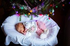 Ett gammalt nyfött för vecka behandla som ett barn flickan som sover nära julgranen Arkivfoto