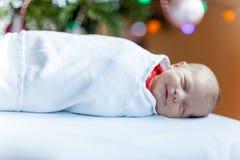 Ett gammalt nyfött för vecka behandla som ett barn slåget in i filt nära julgranen Royaltyfri Foto