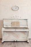 Ett gammalt piano med en ljusstake och en klocka Arkivfoton