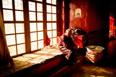 Ett gammalt sammanträde för buddistisk munk i fönstret Lhasa Tibet Arkivfoto