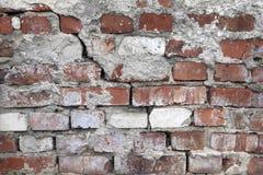 Ett gammalt, skadat, keramiskt, rött, tegelstenvägg med en spricka din bakgrundsdesign Arkivfoton