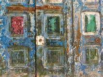 Ett gammalt smutsigt träbräde med fyrkanter av rött och grönt, en abstrakt bakgrund av fördärvar Royaltyfri Foto