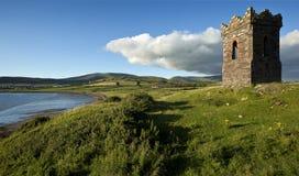 Ett gammalt stenklockatorn över att se Dinglefjärden Co Kerry Ireland som en fiskebåt heads ut till havet Arkivbilder