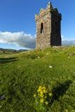 Ett gammalt stenklockatorn över att se Dinglefjärden Co Kerry Ireland som en fiskebåt heads ut till havet Royaltyfri Bild