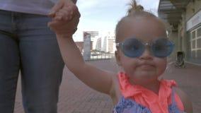 Ett ganska haired behandla som ett barn flickan i mycket stilfull blå rund solglasögon som går rymma moderhanden lager videofilmer