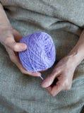 Ett garnnystan i händerna av en äldre kvinna arkivfoton