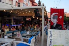 Ett gatakafé med en meny, en turkisk flagga och en stående av ledaren Attarurk Mustafa Kemal royaltyfri fotografi
