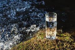 Ett genomskinligt exponeringsglas med att dricka bergvatten i solljus står i mossastenen på solbeame mot en bakgrund Arkivfoto