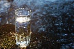 Ett genomskinligt exponeringsglas med att dricka bergvatten i solljus står i mossastenen på solbeame mot en bakgrund Arkivfoton