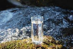 Ett genomskinligt exponeringsglas med att dricka bergvatten i solljus står i mossastenen på solbeame mot en bakgrund Arkivbild