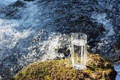 Ett genomskinligt exponeringsglas med att dricka bergvatten i solljus står i mossastenen på solbeame mot en bakgrund Royaltyfri Fotografi