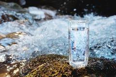 Ett genomskinligt glass exponeringsglas med att dricka bergvatten står i mossastenen på solbeame mot en bakgrund av a Royaltyfria Foton