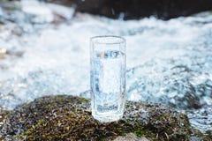 Ett genomskinligt glass exponeringsglas med att dricka bergvatten står i mossastenen på solbeame mot en bakgrund av a Royaltyfri Foto