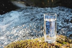 Ett genomskinligt glass exponeringsglas med att dricka bergvatten står i mossastenen på solbeame mot en bakgrund av a Arkivbilder