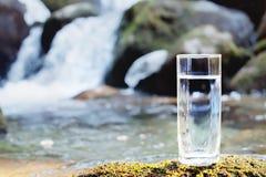 Ett genomskinligt glass exponeringsglas med att dricka bergvatten står i mossastenen på solbeame mot en bakgrund av a Arkivfoto