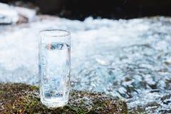 Ett genomskinligt glass exponeringsglas med att dricka bergvatten står i mossastenen på solbeame mot en bakgrund av a Arkivfoton