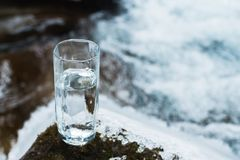 Ett genomskinligt glass exponeringsglas med att dricka bergvatten står i mossastenen på solbeame mot en bakgrund av a Royaltyfri Fotografi