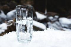 Ett genomskinligt glass exponeringsglas med att dricka bergvatten står i snön mot en bakgrund av en ren bergflod Arkivfoton