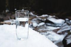 Ett genomskinligt glass exponeringsglas med att dricka bergvatten står i snön mot en bakgrund av en ren bergflod Fotografering för Bildbyråer