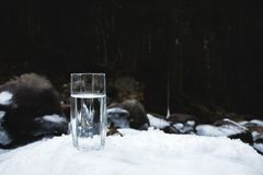 Ett genomskinligt glass exponeringsglas med att dricka bergvatten står i snön mot en bakgrund av en ren bergflod Arkivbilder