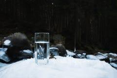 Ett genomskinligt glass exponeringsglas med att dricka bergvatten står i snön mot en bakgrund av en skog i vinter Arkivbild