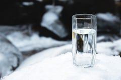 Ett genomskinligt glass exponeringsglas med att dricka bergvattenställningar i snön mot en bakgrund av ett rent frostberg Royaltyfri Foto