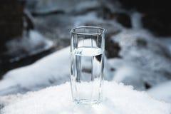 Ett genomskinligt glass exponeringsglas med att dricka bergvattenställningar i snön mot en bakgrund av ett rent frostberg Arkivbilder