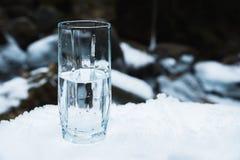Ett genomskinligt glass exponeringsglas med att dricka bergvattenställningar i snön mot en bakgrund av ett rent frostberg Royaltyfri Bild