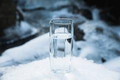 Ett genomskinligt glass exponeringsglas med att dricka bergvattenställningar i snön mot en bakgrund av ett rent frostberg Royaltyfria Bilder