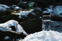 Ett genomskinligt glass exponeringsglas med att dricka bergvattenställningar i snön mot en bakgrund av ett rent frostberg Royaltyfria Foton