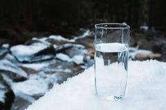 Ett genomskinligt glass exponeringsglas med att dricka bergvattenställningar i snön mot en bakgrund av ett rent frostberg Arkivfoton