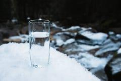 Ett genomskinligt glass exponeringsglas med att dricka bergvattenställningar i snön mot en bakgrund av ett rent frostberg Arkivfoto