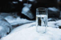 Ett genomskinligt glass exponeringsglas med att dricka bergvattenställningar i snön mot en bakgrund av ett rent frostberg Fotografering för Bildbyråer